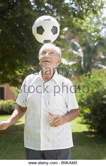 Senior man outdoors balancing soccer ball on head - Stock Image