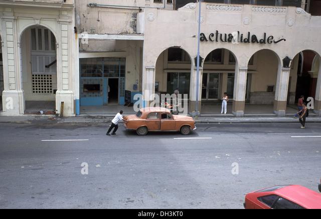 Man pushing an old broken car in the street of Havana, Cuba - Stock Image