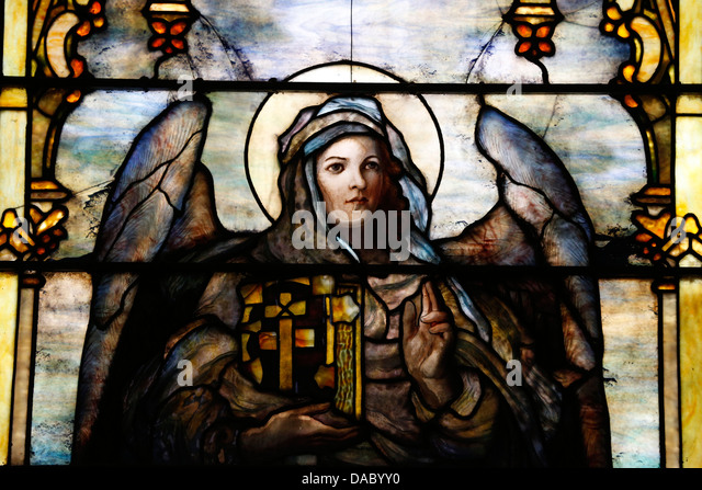 Stained glass window by Louis Comfort Tiffany showing an angel holding the Bible, The American church in Paris, - Stock Image