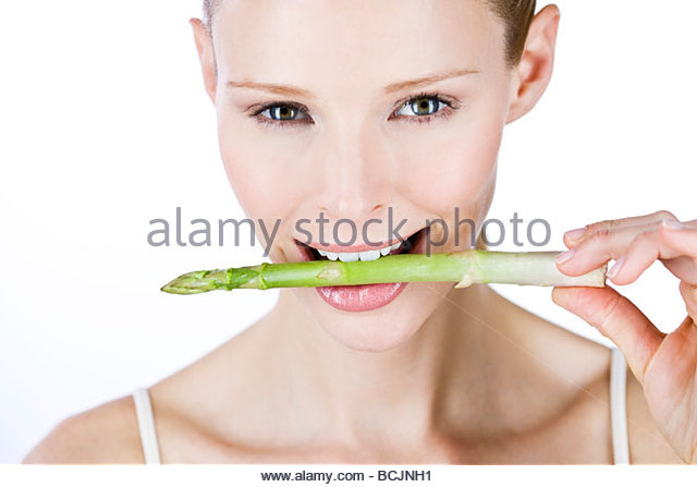 A young woman holding a piece of asparagus in her mouth - Stock Image