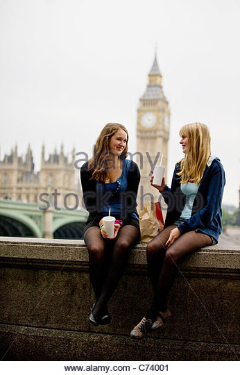 Two teenage girls sitting near Big Ben, having lunch - Stock Image