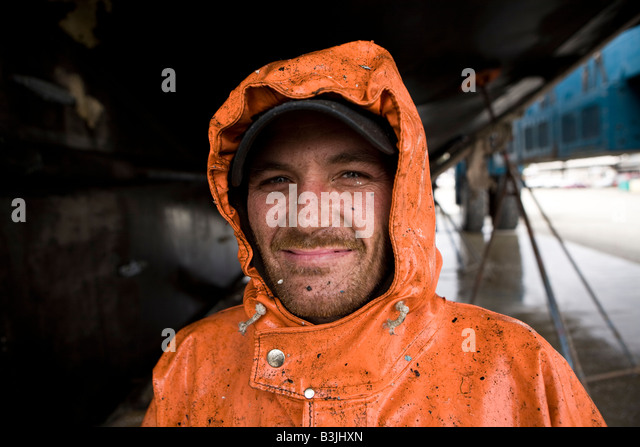 Palmer Robert pressure washes the bottom of an 88 feet long fishing boat Leann in the shipyard in Port Townsend - Stock Image