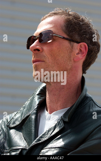 man in his forties wearing a leatherjacket and sunglasses seen in profile - Stock Image