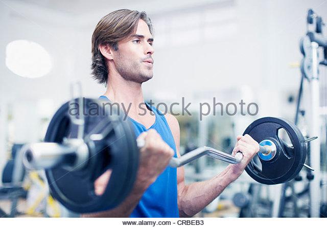 Man lifting barbell in gymnasium - Stock Image