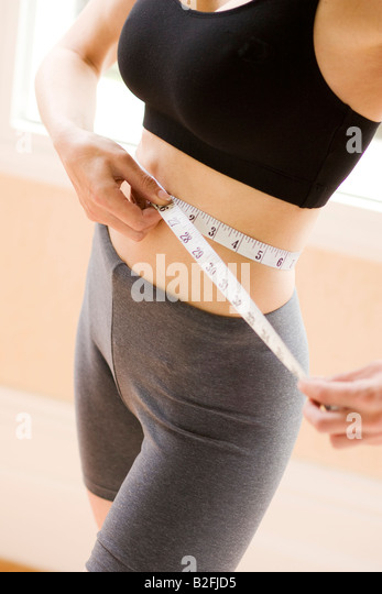 girl female measure waist tape sports diet trim - Stock Image