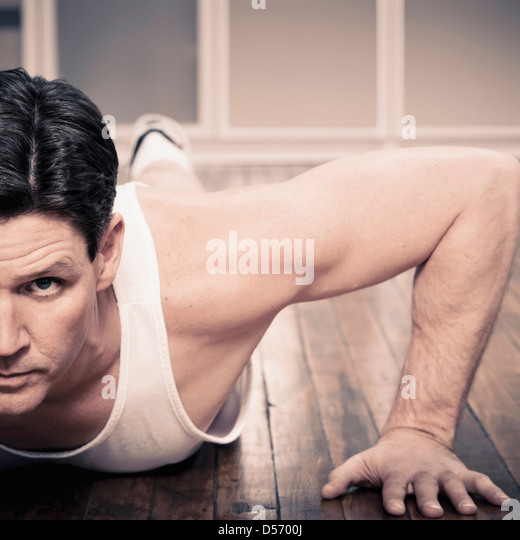 Man doing push ups indoors - Stock Image