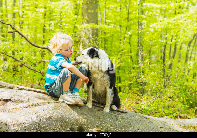 Boy sitting with dog in forest - Stock Image
