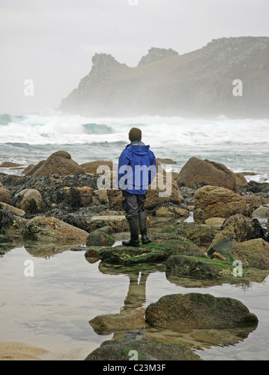 a-man-looks-out-to-sea-and-rocks-at-nanj