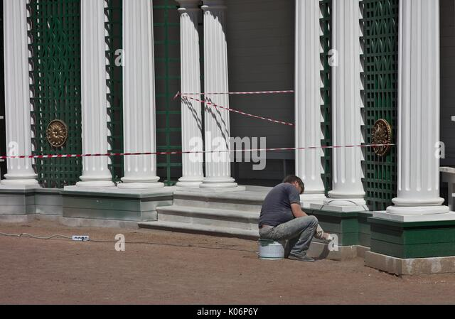 man-using-power-grinder-on-historic-buil