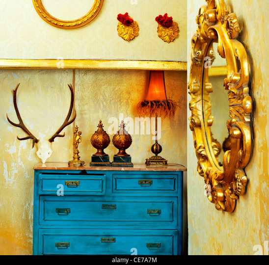 baroque grunge vintage house with blue drawer and golden mirror - Stock Image