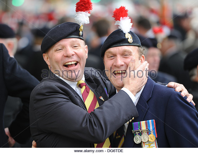 London UK 15th October 2013. In protest at the impending disbandment of the regiment  (2nd batallion, Royal Regiment of Fusiliers) after the current tour of duty in Afghanistan, former members of 2RRF hand in a petition to Downing Street and then march down Whitehall to Parliament. Former comrades in arms share a joke. - Stock Image
