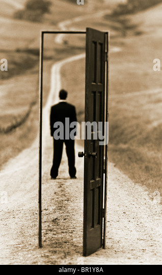 """conceptual photograph of executive man standing on country road framed with an """"open door"""" - Stock Image"""