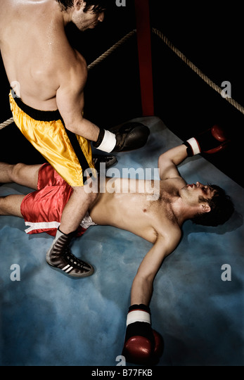 Boxer standing above knocked out opponent - Stock Image