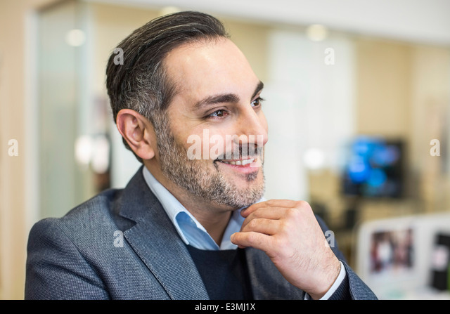 Smiling mid adult businessman looking away in office - Stock Image
