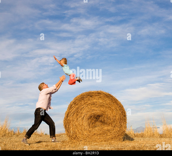 man catching boy jumping from hay bale - Stock Image