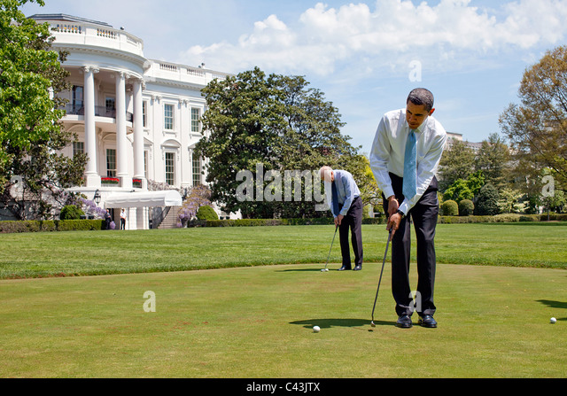 President Barack Obama and Vice President Joe Biden practice their putting on the White House putting green - Stock Image