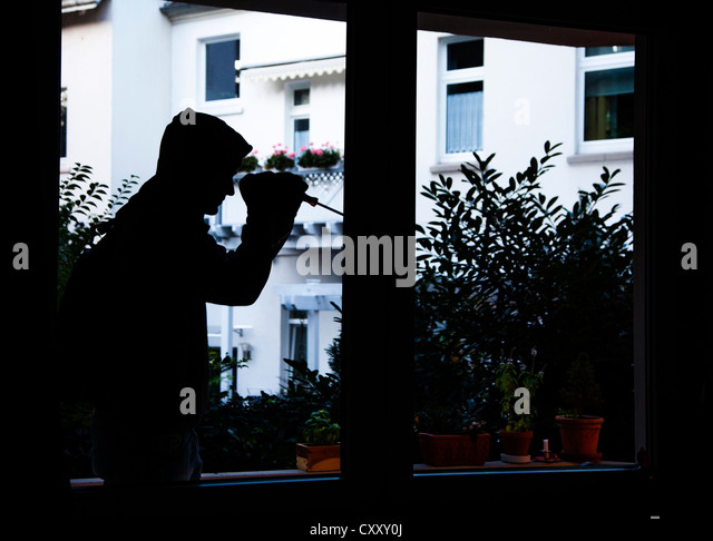 Burglar breaks into an apartment. Symbol image. - Stock Image