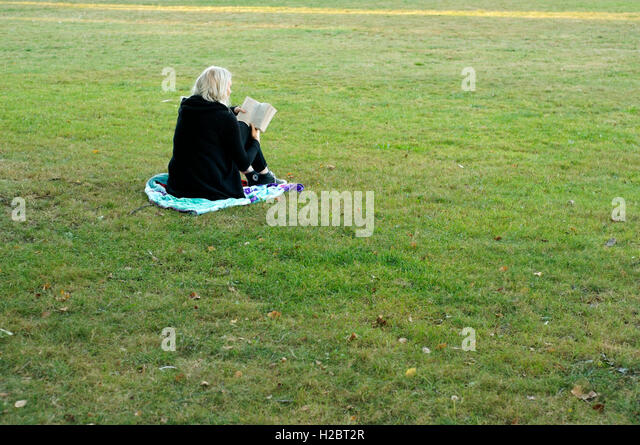 woman-sitting-on-green-grass-reading-a-b