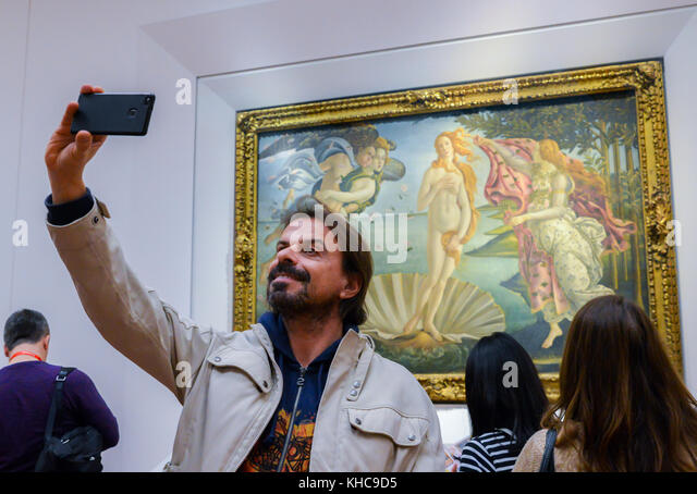 Florence, Italy - October 31st, 2017: Man takes a selfie in front of Birth of Venus by Botticelli at Uffizi Galleries - Stock Image