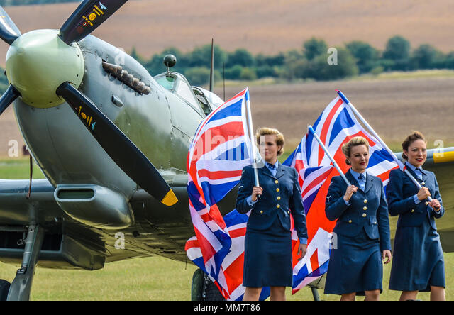 The D-Day Darlings female singing group recently on Britain's Got Talent. Katie Ashby and Nichola Roberts in WRAF wartime uniforms with RAF Spitfire - Stock Image