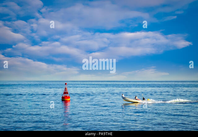 A fast fishing boat moving to a buoy under a perfectly blue sky. - Stock Image
