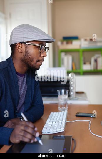 Black designer working at desk - Stock Image