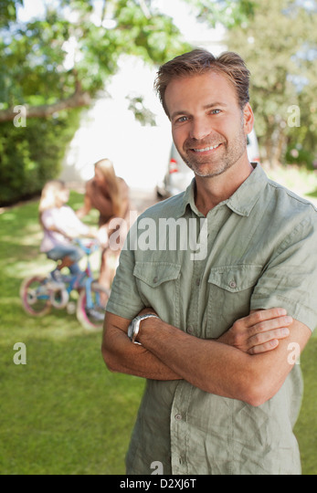Portrait of smiling man with family in background - Stock Image