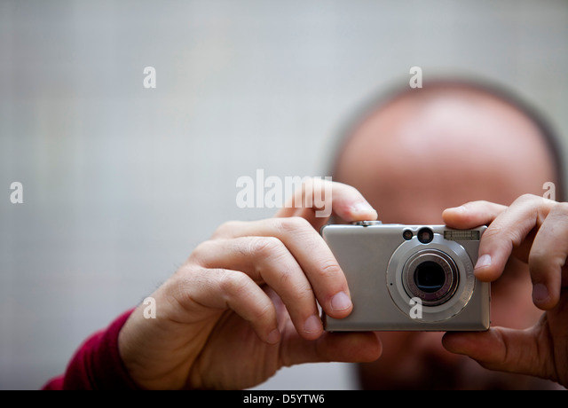 Man Taking a Photograph, Close-up View - Stock Image