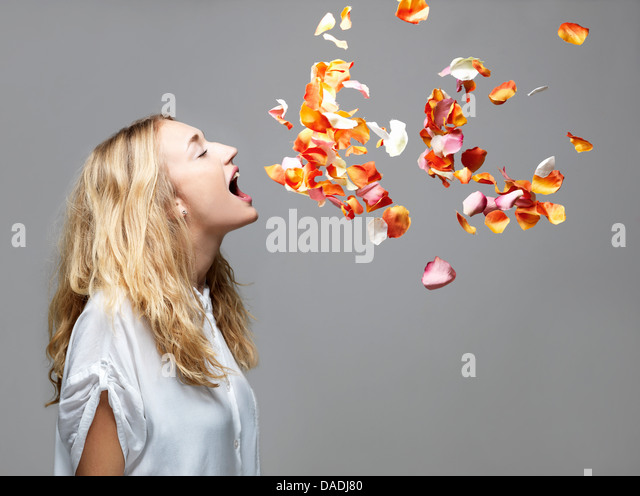 Young woman with mouth open an petals floating in mid air - Stock Image