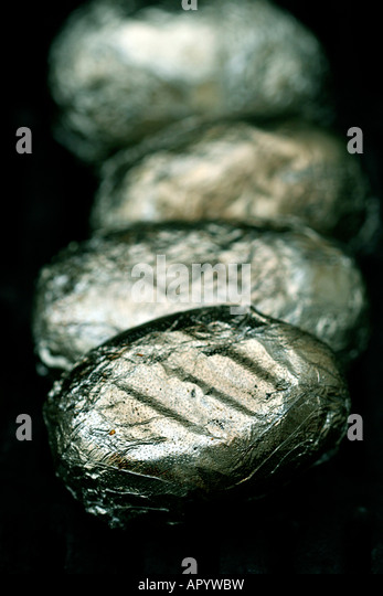 Potatoes wrapped in aluminium sizzling on the BBQ - Stock Image