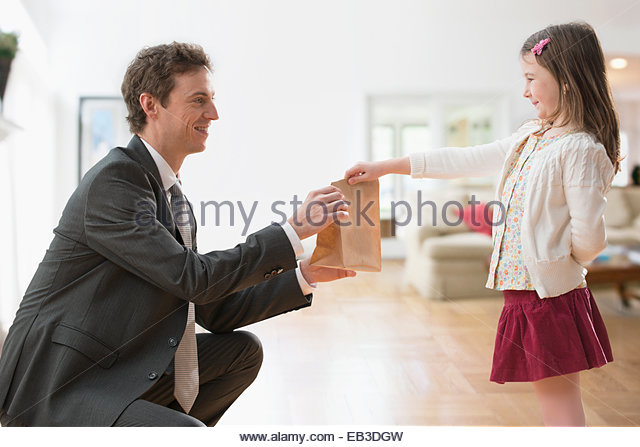 Caucasian girl and father holding bag lunch - Stock Image