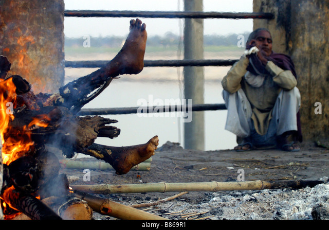 indians burning the funeral pyre on the river ganges