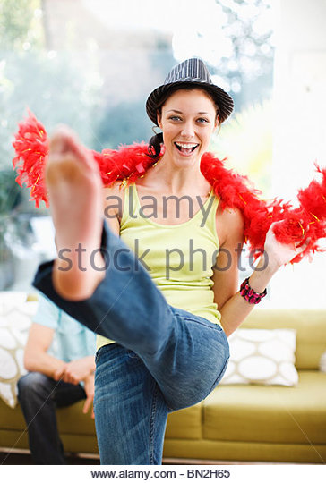 Woman dancing in hat and feather boa - Stock Image