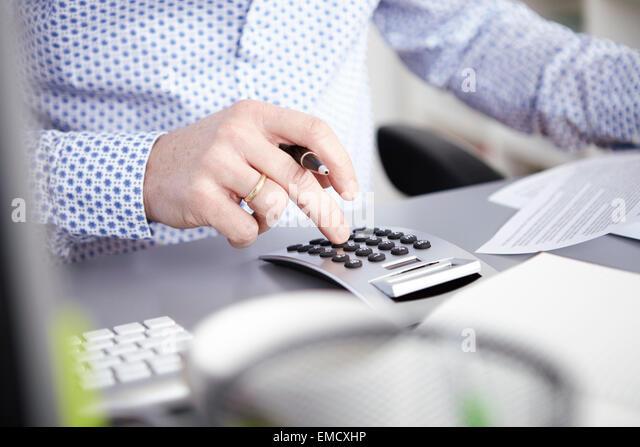 Businessman using calculator - Stock Image