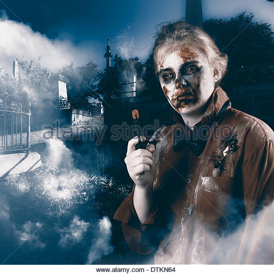 Cruel monster in foggy cemetery late at night holding gun. Grave robber - Stock Image