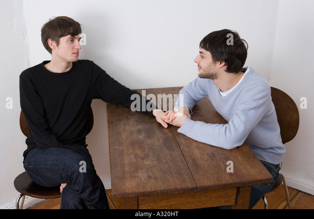 Young gay couple holding hands across table - Stock Image
