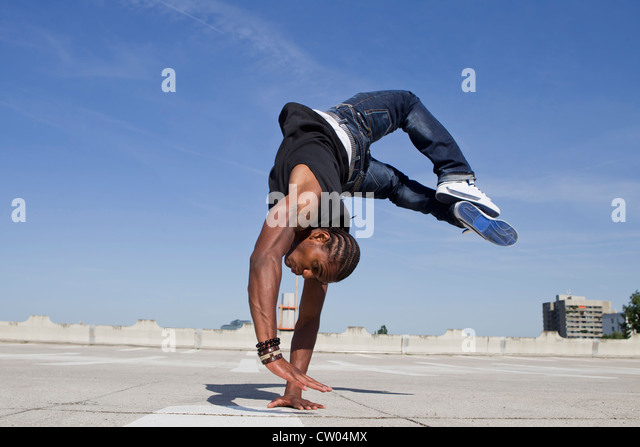 Man doing handstand on rooftop - Stock Image