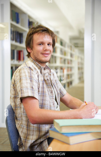 Portrait of young man in library - Stock Image