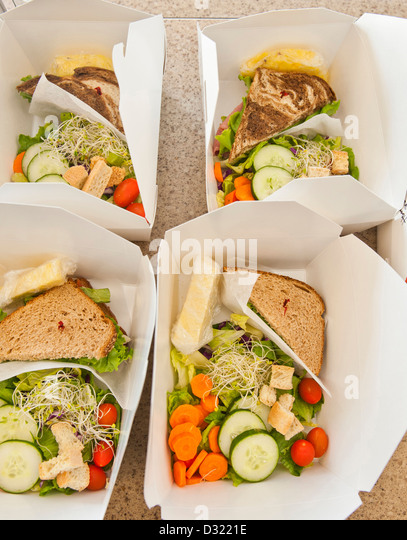 Sliced vegetables and sandwiches in lunch boxes - Stock Image