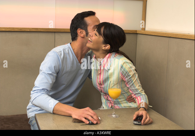 young man and women exchanging welcome kiss in cafe - Stock Image