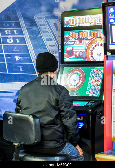 Mature man using fixed odds Roulette machine in Bookmakers. London, England, UK. Machine described as the Crack - Stock Image