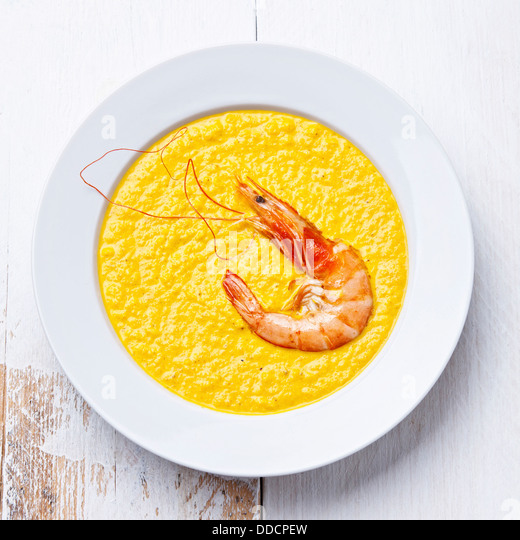 Carrot soup with shrimp on white wooden background - Stock Image
