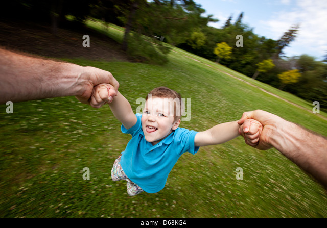 Father Spinning Son Outdoors in Park - Stock Image