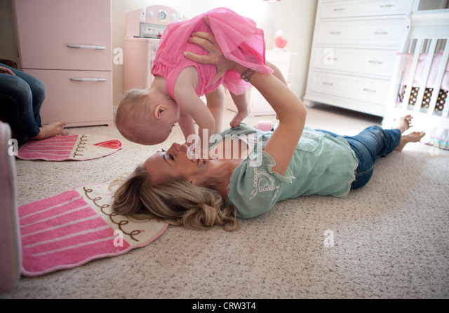 Mom holding her eleven month old girl up and playing in bedroom. - Stock Image