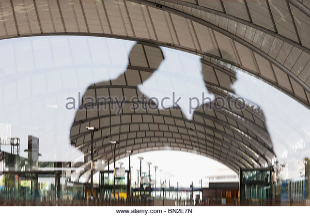 Reflection of business people in train station window - Stock Image