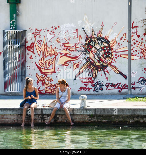 Mother and daughter on the canal in Bohemian Navigli, Milan, Italy - Stock Image