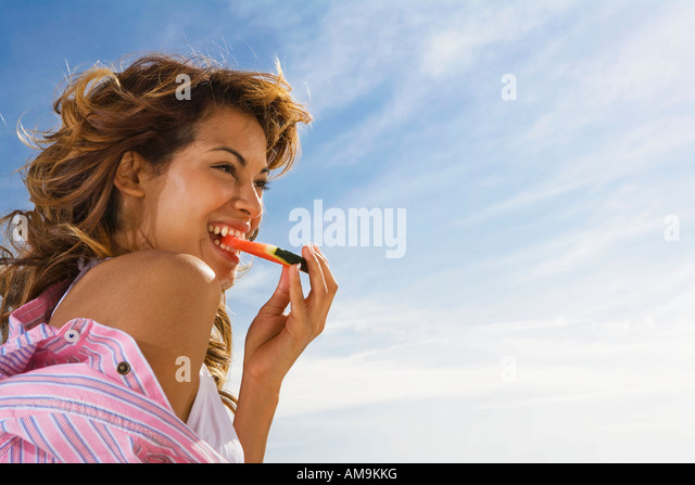 Woman with smile eats watermelon outside. - Stock Image