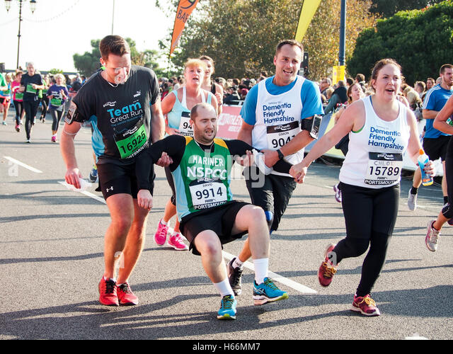 An exhausted runner is helped towards the finish line of the Great South Run 2016 in Portsmouth, England - Stock Image