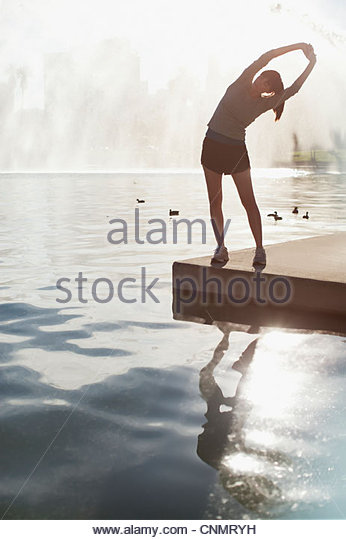 Woman stretching by still lake - Stock Image