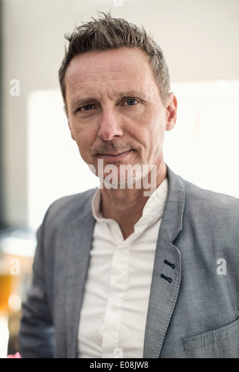 Portrait of confident businessman in office - Stock Image